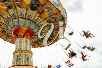 Children riding a colorful merry-go-round at the county fair.