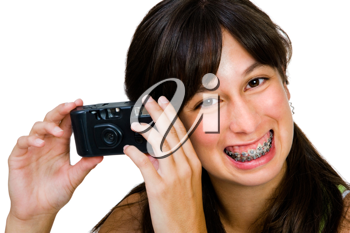 Teenager photographing with a camera and smiling isolated over white
