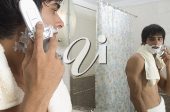 Man talking on a mobile phone in the bathroom