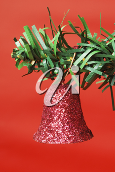 Red Christmas bell hanging on a Christmas tree