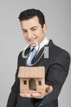 Businessman holding a model home