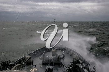 Ship in sea storm. Storm at Baltic sea. Warship training in the Baltic Sea during a storm. Military ship in Baltic sea, Latvia. Military ship at sea during a storm. view from ships the bow.