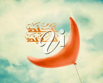 Red Ramadan crescent balloon in vintage blue sky with clouds and Arabic Islamic calligraphy of text Happy Eid.