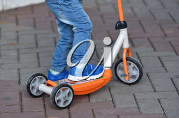 Boy child in blue jeans and sneakers riding a scooter.