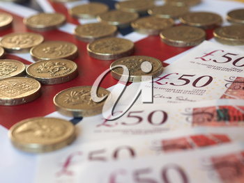 Pound coins and banknotes money (GBP), currency of United Kingdom, over the Union Jack