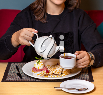 Woman pouring tea with dessert at restaurant