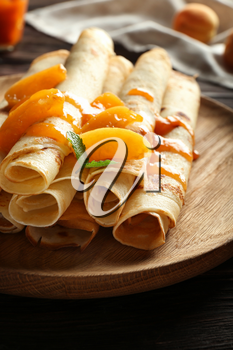 Plate with tasty pancakes and apricot jam on wooden table, closeup