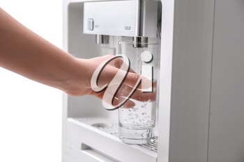 Woman filling glass with water from cooler, closeup