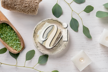 Composition with burning candles, eucalyptus branches, sea salt and soap bar on white background
