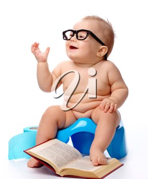 Royalty Free Photo of a Child Wearing Glasses While on a Potty With a Book