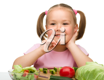 Royalty Free Photo of a Little Girl With Vegetables in Front of Her