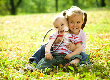 Royalty Free Photo of Two Children Sitting on the Grass in Autumn