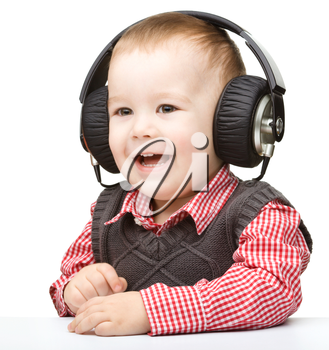Cute little boy enjoying music using headphones, isolated over white