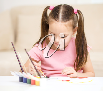 Cute cheerful child play with paints while sitting at table