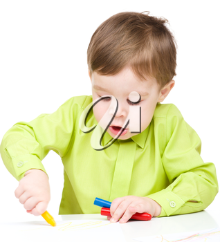 Little boy is drawing using crayon, isolated over white