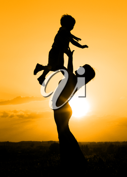 Silhouette of mother playing with her son backlit by sunset