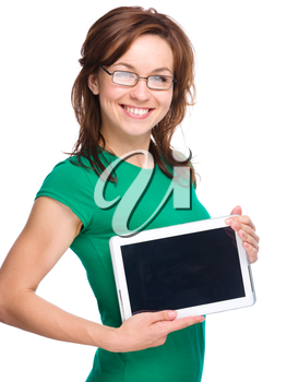 Young cheerful woman is showing blank tablet, isolated over white