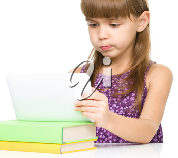 Young girl is using tablet and making funny face while studying, isolated over white