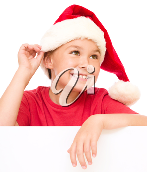 Little girl in santa hat is holding blank board and showing ear like listening, isolated over white