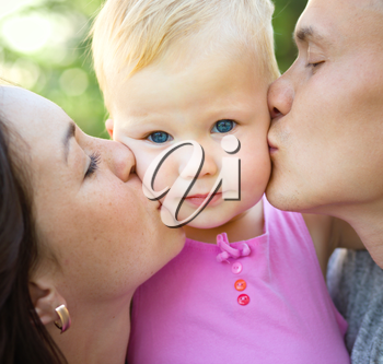 Parents kissing their child, outdoor shoot