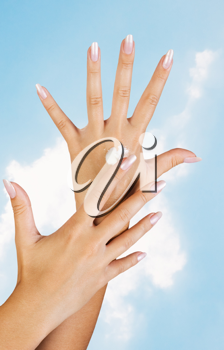 Royalty Free Photo of a Woman's Hands With Lotion Against a Sky