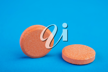 two orange tablets on a blue background