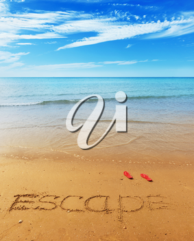 Escape message on the beach sand - vacation and travel concept