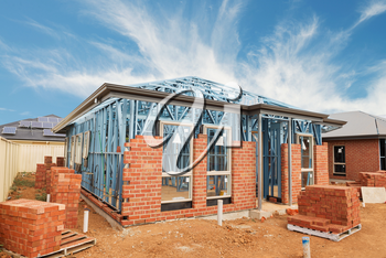 New residential construction brick home with metal framing against a blue sky