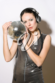 Portrait of beautiful young woman in headphones with a mirror ball