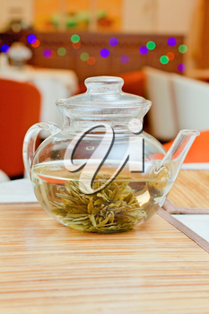 Glass teapot with green tea on a table