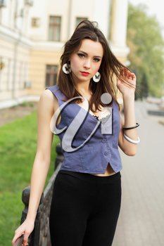 Pretty young woman posing outdoors in grey vest