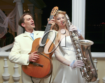 Royalty Free Photo of a Bride and Groom Playing Instruments