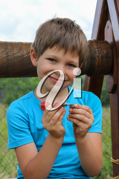 Smiling boy in front of old style wooden well