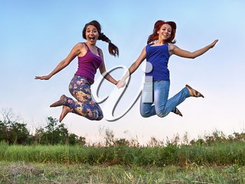 Two girls jumping in the air holding hands