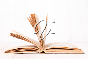 Open book on  white wood background. With place for text