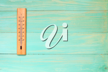 Thermometer on the wooden wall showing high temperature near 30 degrees