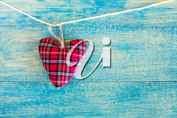 Decorative fabric heart  hanging on the blue wooden background