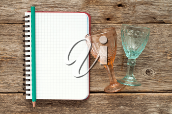Two wine glasses and blank notebook for menu or cocktail recipes