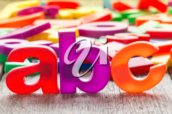 ABC spelling and pile of colorful plastic letters on wooden background