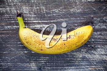 Yellow banana on dark wooden background. Top view.