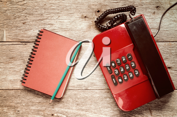 Old telephone and personal organizer with pencil on wooden background