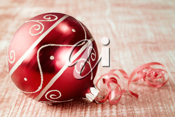 Christmas ball with ribbon on wooden background