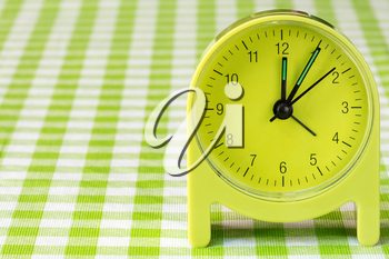 Green alarm clock on the table with checkered tablecloth