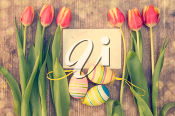 Easter eggs,fresh spring tulips and blank card for copy-space