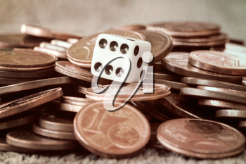 Dice and coin pile on wooden table