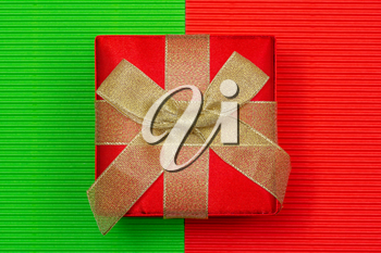 Beautiful gift box with golden bow on the colorful paper background