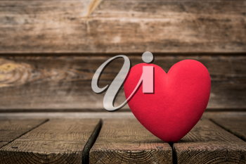 Red heart on the weathered wooden background. Love and romance