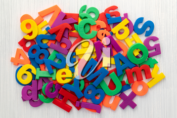 A pile of coloured magnetic letters and numbers over a wooden table