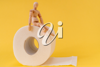 Wooden mannequin sit on a roll of toilet paper. Concept for constipation and bowel movement