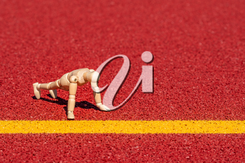 Wooden man doing  push ups on running track. Healthy life concept.